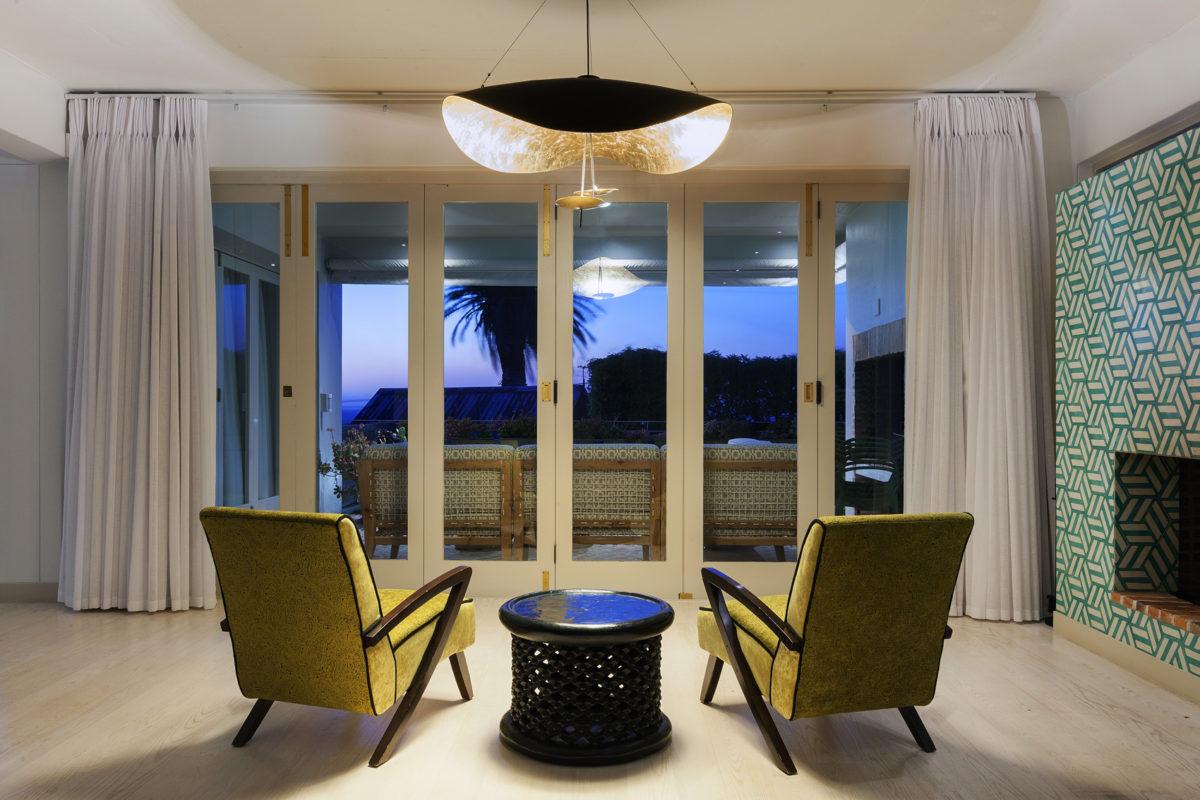 soggiorno vetrata vista mare con lampadario nero e oro di catellani&smith